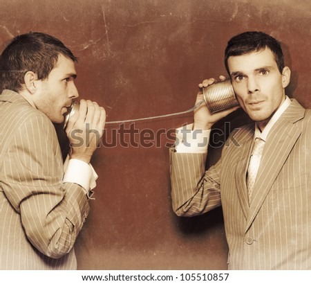 Vintage Photograph Of Two Business People Exchanging Information Down The Line Of A Tin Can Telephone In A Retro Communication Conceptual - stock photo