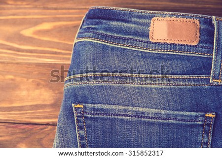 Vintage picture of blue jeans with half of back pocket and brown leather tag on wood table background. Shallow depth of field.  - stock photo