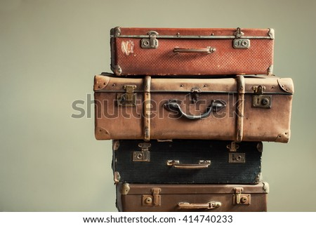 Vintage Pile Ancient Suitcases Form of Tower Design Concept Travel Luggage Traveler on Shabby Beige Background - stock photo