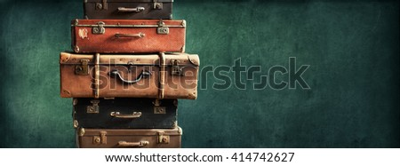 Vintage Pile Ancient Suitcases Form of Tower Design Concept Travel Luggage Traveler on Shabby Black Background Long Format - stock photo
