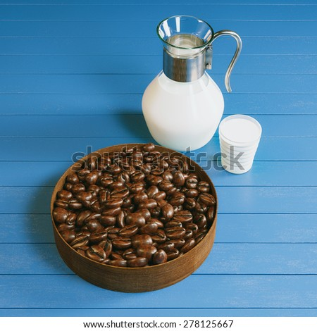 Vintage pitcher and glass full of organic bio milk and plate with roasted coffee beans on blue wooden surface. Picture of breakfast in cafe. - stock photo