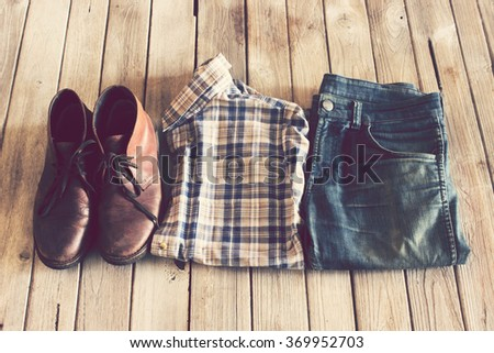Vintage,Plaid shirt,Jean and leather shoes on wood background - stock photo