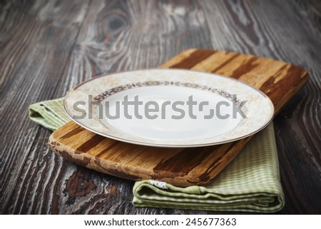vintage plate on green  kitchen towel on wooden background. kitchen utensils - stock photo