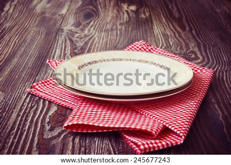 vintage plate on red kitchen towel on wooden background. kitchen utensils, toned image - stock photo