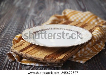 vintage plate on yellow kitchen towel on wooden background. kitchen utensils - stock photo