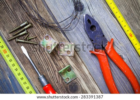 Vintage pliers, screwdriver, screws, wire, angles and roulette. Still life with old tools - stock photo