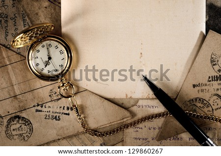 vintage pocket clock and pen on old letters texture - stock photo