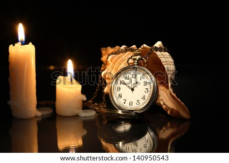 Vintage pocket watch near lighting candles and shell - stock photo