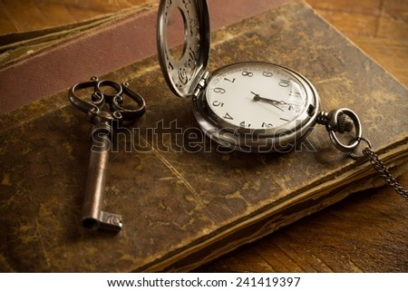 Vintage pocket watch, old book and a brass key on a vintage surface - stock photo