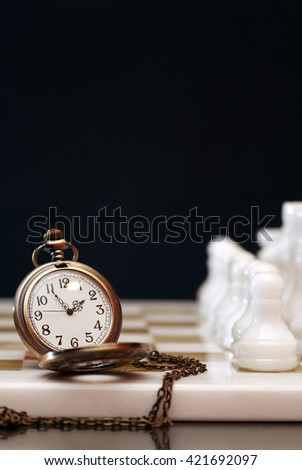 Vintage pocket watch on chessboard against dark background - stock photo