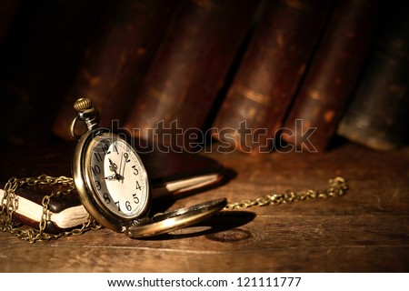 Vintage pocket watch on wooden surface against old books - stock photo