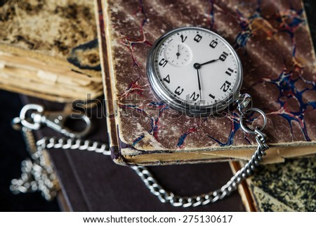 Vintage pocket watch with a steel chain lie on a pile of old books - stock photo