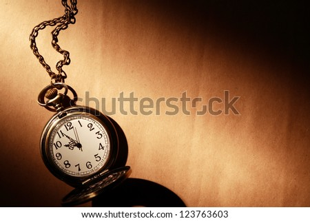 Vintage pocket watch with chain on old paper under beam of light - stock photo