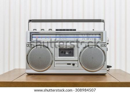 Vintage portable boom box style radio cassette player on old wood table.   - stock photo