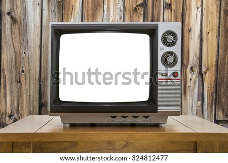 Vintage portable television with cut out screen and rustic cabin wall. - stock photo