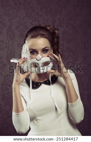 vintage portarit of elegant woman in white with carnival mask . she is posing at the camera . - stock photo