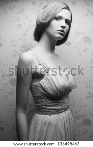 Vintage portrait of a glamorous doll-like retro girl posing in gorgeous classic dress . Hollywood style (film noir). Black and white (monochrome) studio shot - stock photo