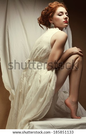 Vintage portrait of a glamorous queen like girl in white dress posing in her bedroom. Perfect hairdo and wild glance. Retro style. Indoor shot - stock photo