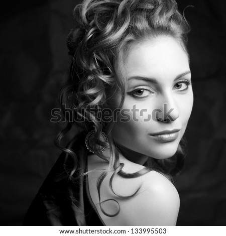 Vintage portrait of a glamorous queen-like young woman posing over wrinkled black paper background. Retro (Hollywood) style. Film noir. Old classic movie. Black and white (monochrome) studio shot - stock photo