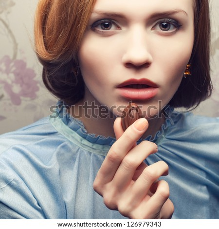 Vintage portrait of a glamorous red-haired (ginger) girl in blue dress eating chocolate candy. Close up. Studio shot - stock photo