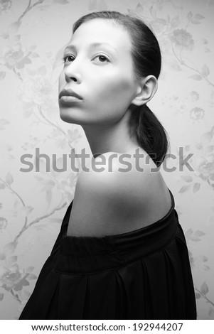 Vintage portrait of a glamorous retro girl posing in gorgeous classic dress . Hollywood style (film noir). Perfect skin and hairdo. Close up. Black and white (monochrome) studio shot  - stock photo