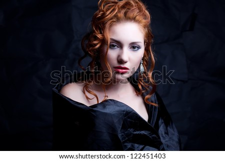 Vintage portrait of a glamourous red-haired queen like girl over wrinkled black paper background. Retro style. Studio shot - stock photo