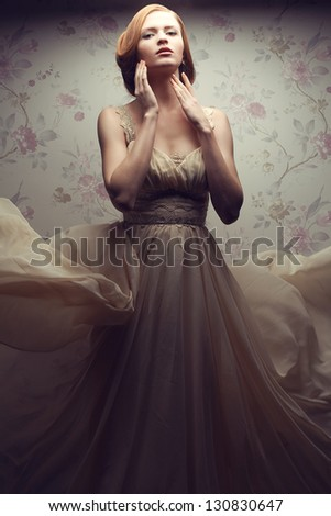 Vintage portrait of a happy glamorous red-haired (ginger) girl posing in great flying beige dress and dancing. Studio shot - stock photo