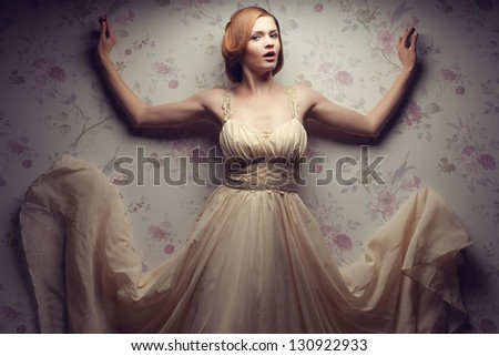 Vintage portrait of a happy glamorous red-haired (ginger) girl posing in great flying beige dress, dancing with hands up and singing. Retro style. Studio shot - stock photo