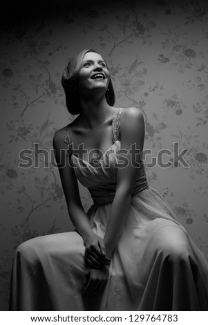 Vintage portrait of a happy glamorous retro girl posing in gorgeous classic dress and laughing. Hollywood style (film noir). Studio shot - stock photo