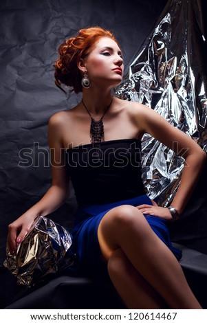 Vintage portrait of a seductive ginger model with silver foil posing over wrinkled black paper background. studio shot - stock photo