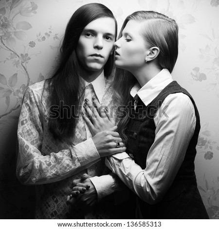 Vintage portrait of beautiful long haired people: handsome boy with brown hair and whispering gorgeous blonde girl posing together. Retro (classic) style. Black and white (monochrome) studio shot. - stock photo