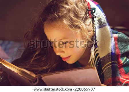 Vintage portrait of cute curly school girl reading a book in cold day - stock photo