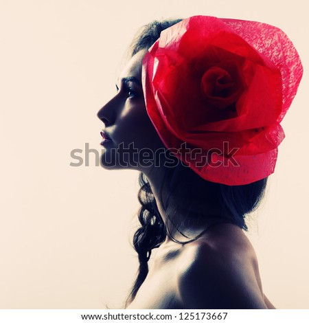 Vintage portrait of fashion glamour girl with red flower in her hair, over white. Studio shot. - stock photo