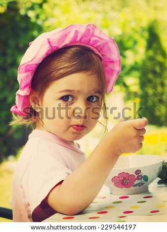 Vintage portrait of little cute girl in a purple cap eats with appetite a breakfast  in outdoor cafe  - stock photo