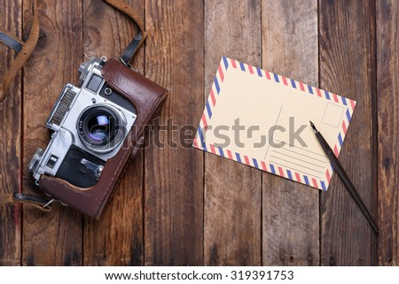 Vintage post card and retro camera on old wooden table - stock photo