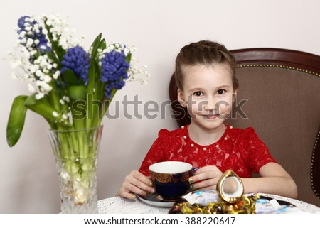 vintage preteen girl in red dress drink tea time with hyacinth bouquet in crystal vase close up portrait  - stock photo