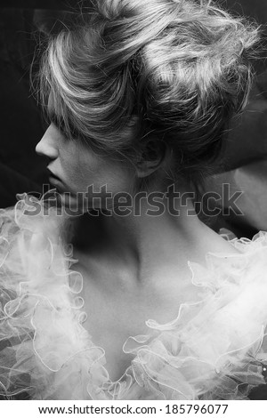 Vintage profile portrait of a crazy queen like girl posing over wrinkled black paper background. Retro style. Black and white (monochrome) studio shot - stock photo