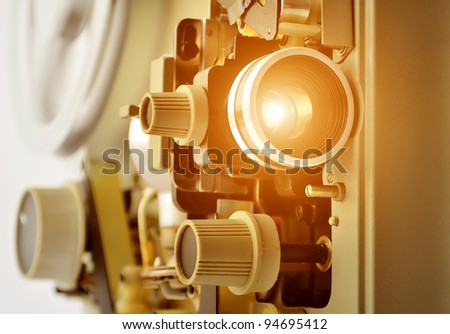 vintage projector turned on. The light exiting the lens. brown background - stock photo