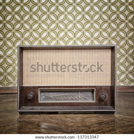 vintage radio receiver device on the weathered wooden parquet floor in vintage room with old fashioned wallpaper, toned - stock photo