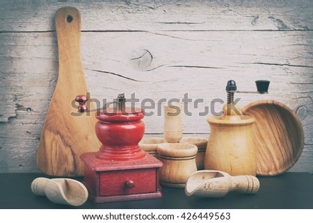 Vintage red and wooden pepper grinders with some kitchen utensils - stock photo