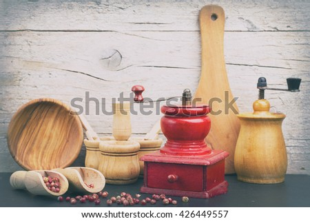 Vintage red and wooden pepper grinders with some wooden utensils - stock photo