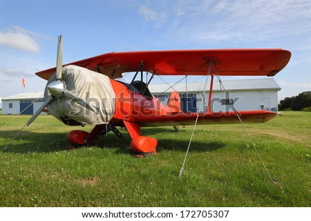 Vintage Red Biplane. A vintage red biplane secured to the ground at a small airfield.  - stock photo