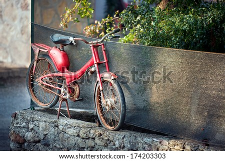Vintage red motorbike, moped in the street - stock photo
