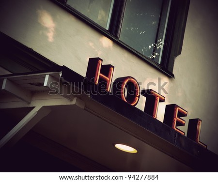 Vintage red neon sign on small village hotel - stock photo