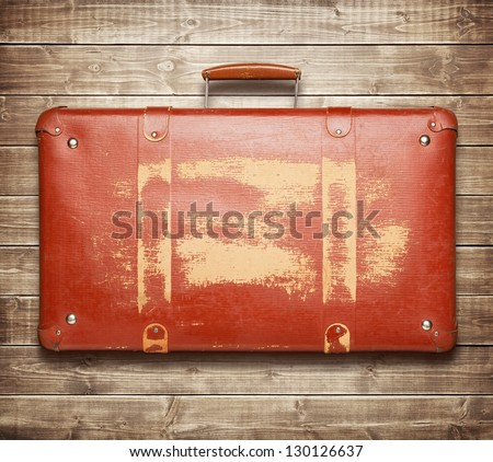 Vintage red suitcase on wooden background - stock photo