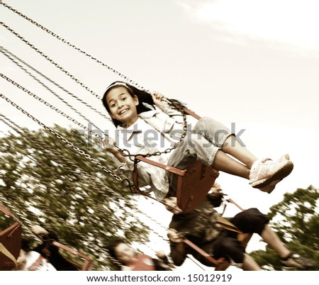 Vintage rendition of a young girl thrilled being on the swing at the steam fair. - stock photo
