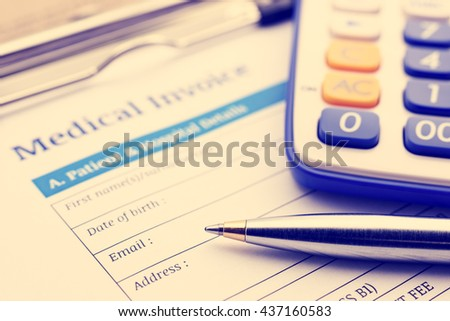 Vintage / retro color style : Blue ballpoint pen, a calculator and a medical invoice on a clipboard. - stock photo