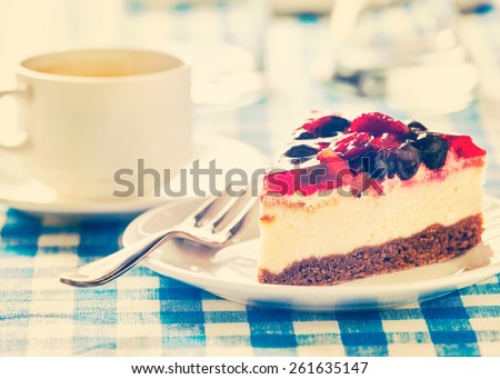 Vintage retro effect filtered hipster style image of dessert fruit cheese cake on plate with fork and coffee cup on blue checkered tablecloth - stock photo