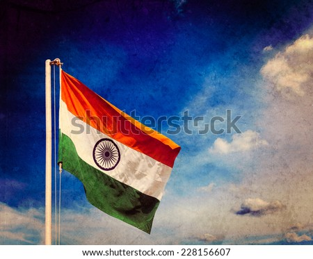 Vintage retro effect filtered hipster style image of  India indian flag in blue sky with copyspace with grunge texture overlaid - stock photo