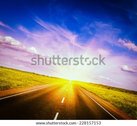 Vintage retro effect filtered hipster style image of travel concept background - road in blooming spring meadow on sunset - stock photo